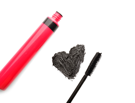 Mascara with drawn heart on white background