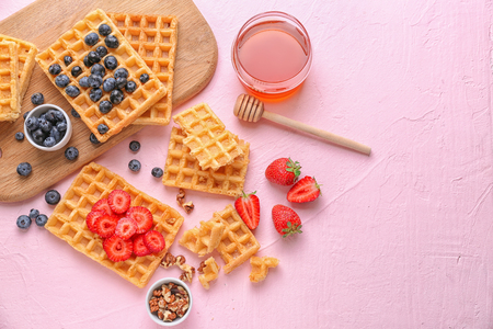 Composition with delicious waffles and berries on color background Stock Photo