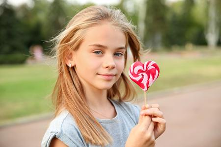 Cute little girl with heart-shaped lollipop outdoors
