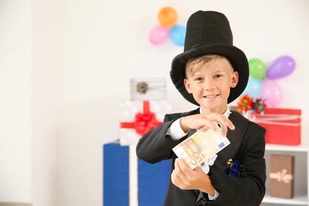 Cute little magician showing trick with money indoors Standard-Bild - 119755448