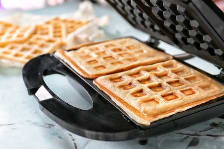 Preparing of waffles in modern maker on light table