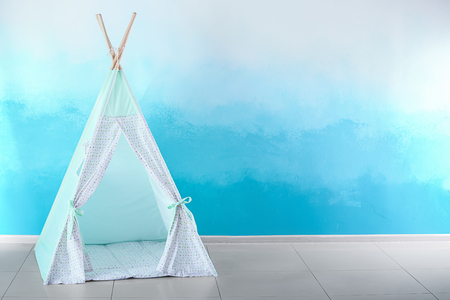 Cozy play tent for kids near color wall Stock Photo