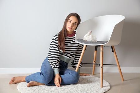 Beautiful young woman and cute bunny on chair near light wall Standard-Bild