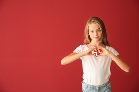 Cute little girl with small heart on color background