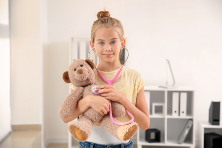 Cute little girl with stethoscope and teddy bear at home