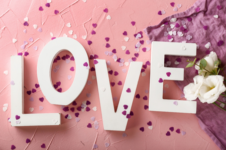 Word LOVE with confetti and flowers on color background