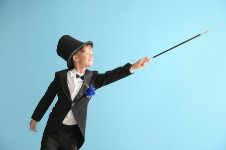 Cute little magician showing trick on color background Stock Photo