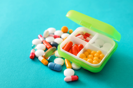 Plastic container with pills on color background