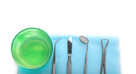 Dentist's tools and glass with mouthwash on white background Foto de archivo