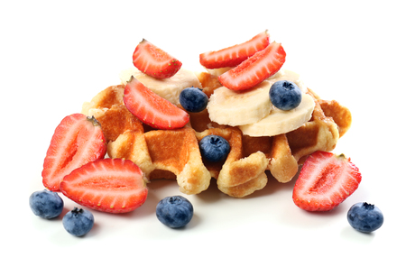 Delicious waffle with berries and banana on white background
