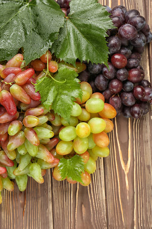 Different types of ripe sweet grapes on wooden background Standard-Bild