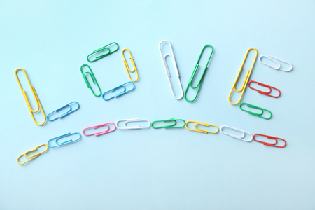 Word LOVE made of colorful clips on light background