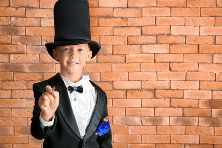 Cute little magician against brick wall