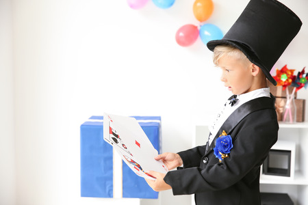 Cute little magician with cards indoors Stock Photo