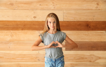 Cute little girl making heart with her hands on wooden background
