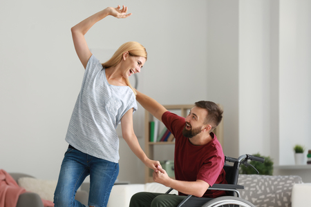 Man in wheelchair with beautiful woman dancing at home 写真素材