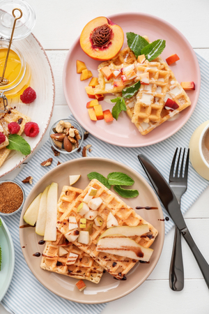 Delicious waffles with fruits and berries on plates, top view