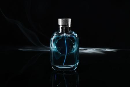 Botella de perfume con humo sobre fondo oscuro