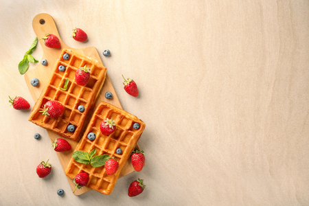 Delicious waffles with berries on wooden board Standard-Bild - 115141638