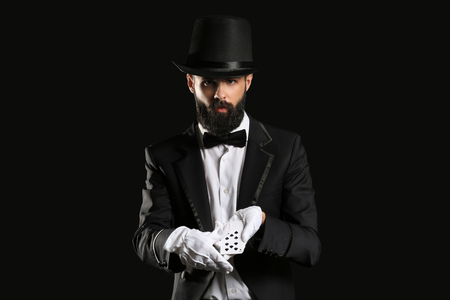 Magician with cards on dark background Stock Photo