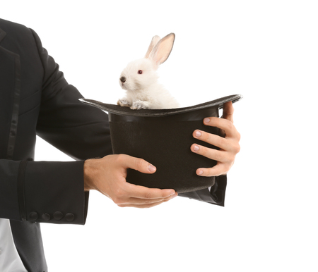 Magician holding hat with rabbit on white background Standard-Bild