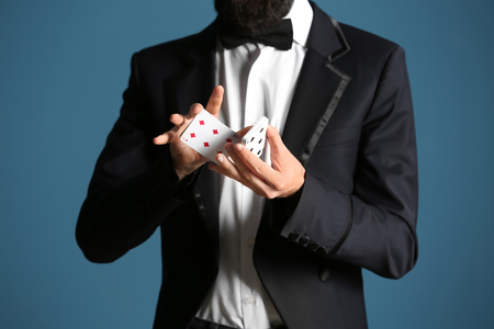 Magician showing tricks with cards on color background, closeup