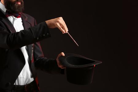 Magician showing tricks on dark background