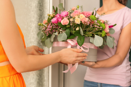 Young woman receiving gift box with beautiful flowers from courier