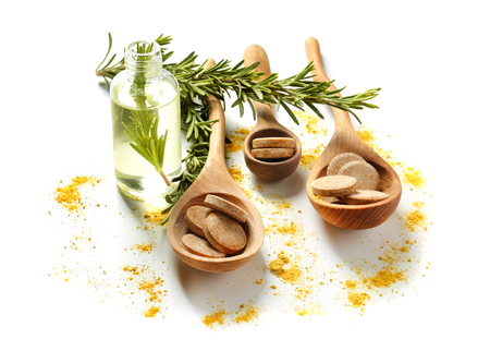 Wooden spoons with tablets, rosemary and essential oil on white background Banco de Imagens