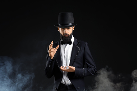 Magician showing tricks in smoke on dark background Stock Photo