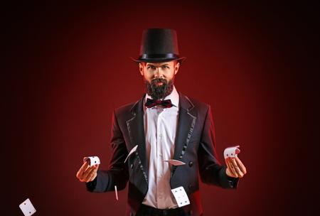 Goochelaar die trucs toont met kaarten op een donkere achtergrond Stockfoto