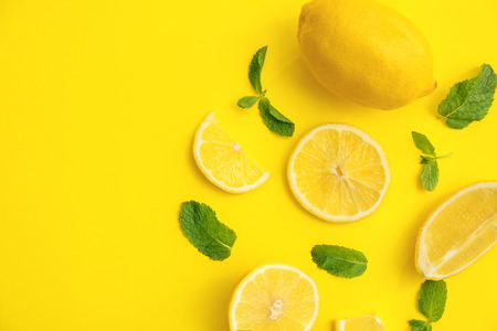 Fresh lemons and green leaves on color background, flat lay
