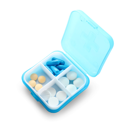 Plastic container with different pills on white background