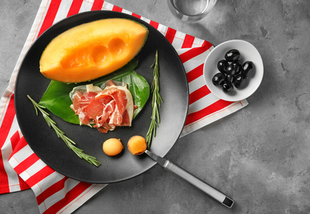 Plate with delicious melon and prosciutto on table, top view