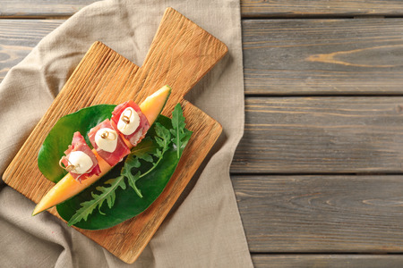 Delicious canape with melon, prosciutto and mozzarella on wooden board, top view Standard-Bild