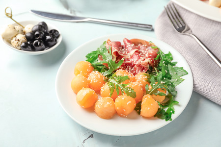 Plate with delicious melon balls and prosciutto on table Standard-Bild