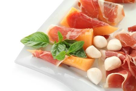 Delicious melon, prosciutto and mozzarella on plate, closeup