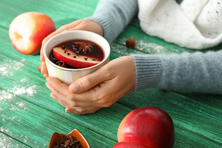 Woman holding cup of delicious mulled wine on color wooden table, closeup Stock Photo