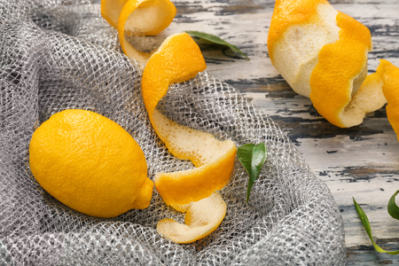 Fresh lemons and peel on wooden table Imagens