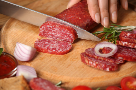 Woman cutting smoked sausage on wooden board, closeup
