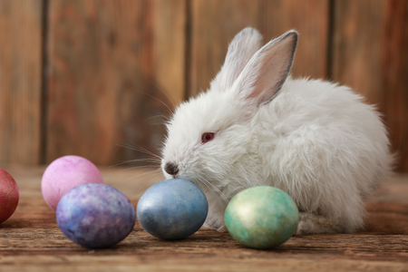 Cute bunny and Easter eggs on wooden background Stock Photo