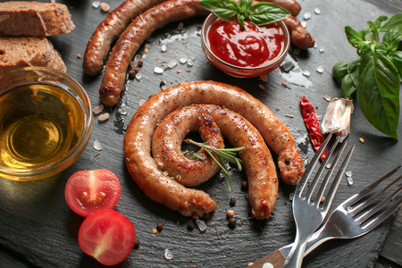Spicy fried sausages on slate plate Banco de Imagens