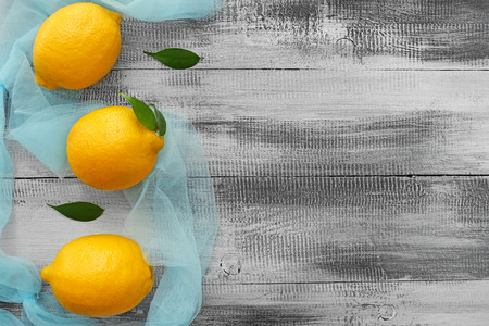 Fresh ripe lemons with color cloth on wooden background