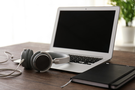 Headphones with laptop and notebook on wooden table 版權商用圖片