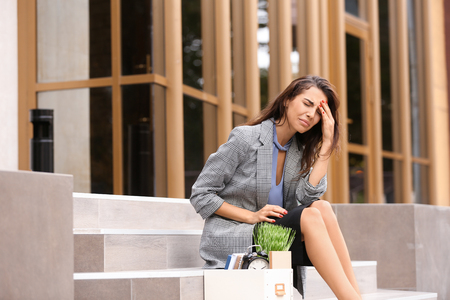 Fired woman with personal stuff sitting on stairs outdoors