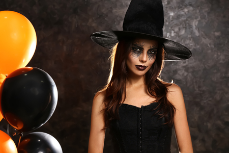 Beautiful woman dressed as witch for Halloween with balloons on dark background
