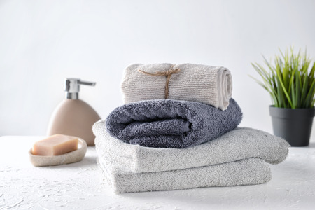 Clean folded towels on white table Stock Photo