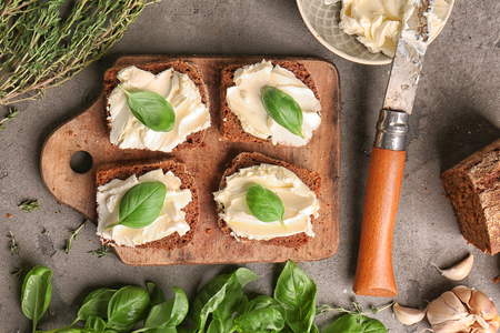 Tasty sandwiches with spread and fresh herbs on wooden board, top view