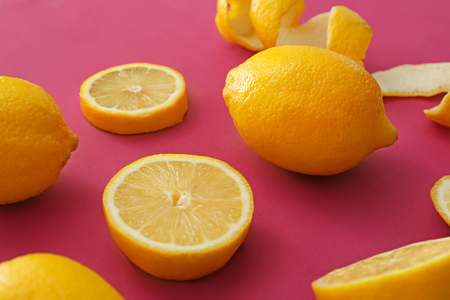 Fresh ripe lemons with slices on color background