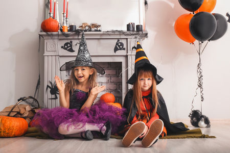 Cute little girls in Halloween costumes near decorated fireplace